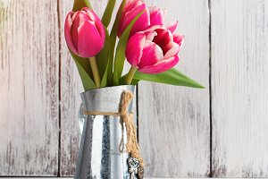 Pink tulips in rustic pitcher