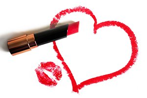 Red lipstick, painted heart and imprint of lips on a white background