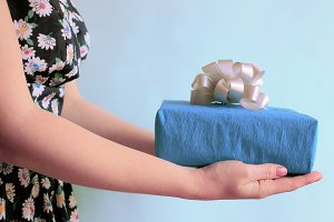 Present in woman's hands in retro dress on a blue background