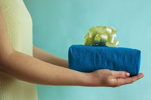 Gift box in woman's hands, give and receive a gift, yellow and blue