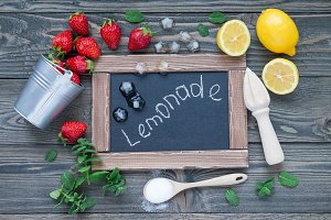 Ingredients for homemade strawberry lemonade on wooden table, around chalk board, top view
