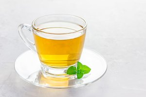 Herbal mint tea in a glass cup with fresh peppermint on background, horizontal, copy space