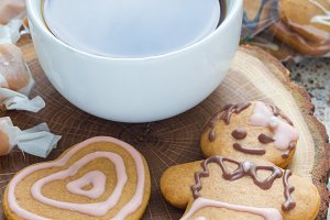 Sweet gifts for hollydays. Homemade christmas gingerbread cookies and cup of coffee on wooden board, vertical.