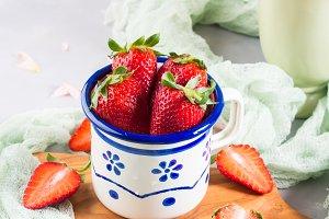 Ripe strawberries in enamel mug