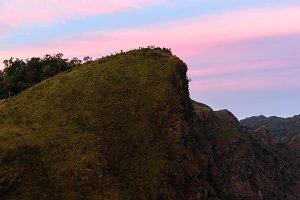 Hikes on mountain peak at sunset.