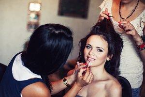 wedding. Young beautiful girl applying make-up by make-up artist