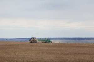 Old-fashioned tractor sowing crops at field