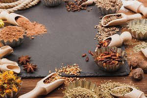 Different spices in bakeware with wooden scoops on the slate slone