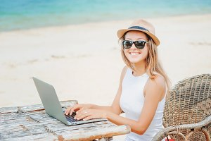Young woman working in laptop on the beach. Freelance work