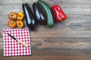 Vegetable background, knife and napkin checkered on wooden background. Vegetables.