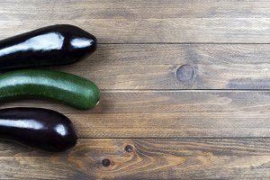 Background of aubergines and a pickle on wooden background. Vegetables.