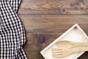 Background of plaid kitchen tablecloth, wooden box and cotlery on wooden background. Copy space.