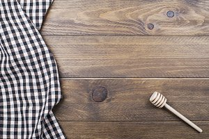 Background of plaid kitchen tablecloth and cookware on wooden background. Copy space. Horizontal shoot.
