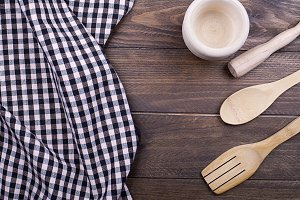 Background of plaid kitchen tablecloth, cookware and cutlery on wooden background. Copy space. Horizontal shoot.
