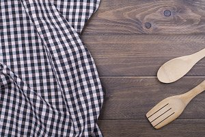 Background of plaid kitchen tablecloth and cutlery on wooden background. Copy space. Horizontal shoot.