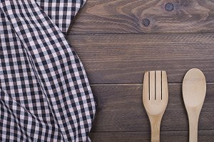 Background of plaid kitchen tablecloth and cutlery on wooden background. Copy space. Concept.
