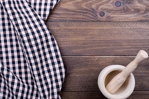 Background of plaid kitchen tablecloth and cookware on wooden background. Copy space. Concept.