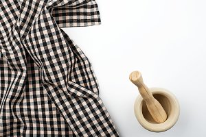 Background of checked kitchen tablecloth and wooden cookware on white background. Copy space. Kitchen.