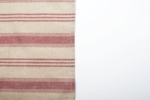 Background of striped kitchen tablecloth over white background. Copy space.