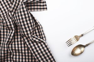 Background of plaid kitchen tablecloth and cutlery on white background. Copy space. Horizontal shoot.