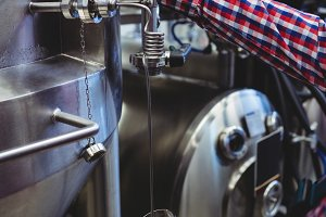 Manufacturer filling beer glass at storage tank