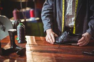 Shoemaker examining a shoe