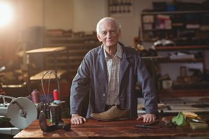 Portrait of shoemaker standing in workshop