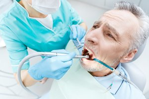 dentist curing scared mature patient