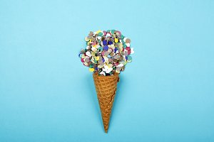 Iced cone with serpentine on blue background. Conceptual, party.