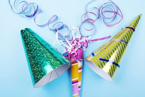 Background of party items and celebrations on blue background. Party hats and colorful ribbons. Horizontal shoot.