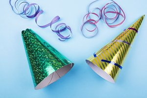 Background of party items and celebrations on blue background. Party hats and colorful ribbons.