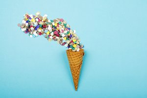 Iced cone with serpentine on blue background. Conceptual, party. Horizontal shoot