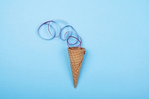 Ice cream cone with colored ribbon on blue background. Conceptual, party. Horizontal shoot