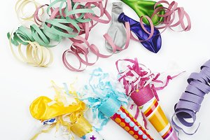 Background of party items and celebrations on white background. Colorful ribbons, paper trumpets and balloons.