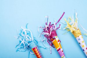 Background of party items and celebrations on blue background. Colorful trumpets.