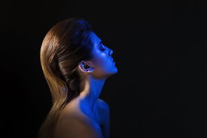 Studio portrait of a girl lit in blue light