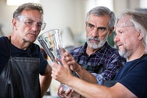 Glassblowers examining glass vase in glassblowing factory