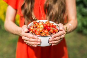 young girl holding bowl of cherries