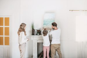Happy family hanging picture