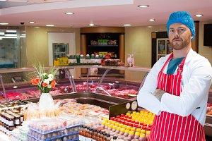 Butcher standing in meat shop with his hands crossed