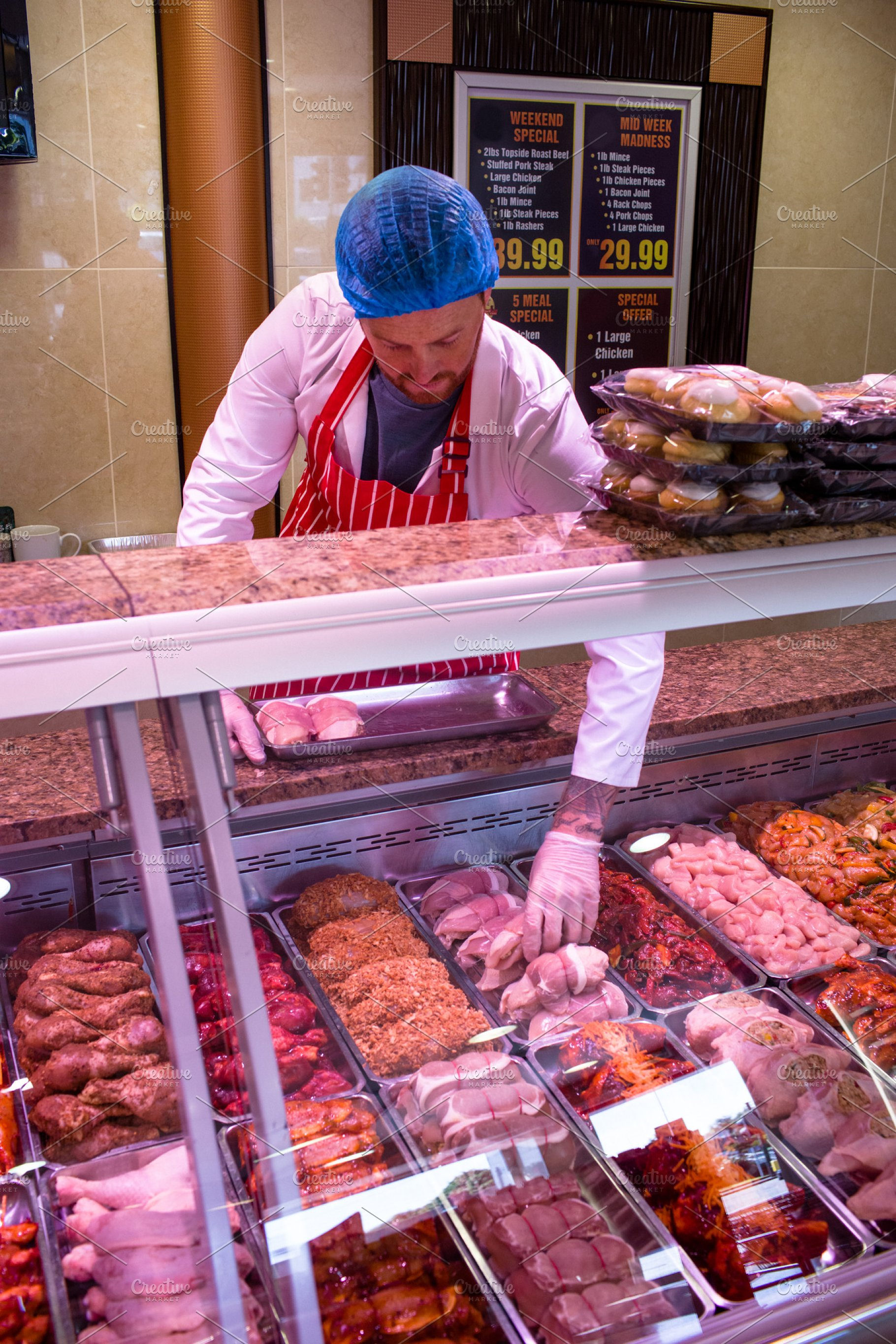 Butcher Checking The Meat Display
