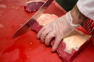 Hands of butcher slicing red meat