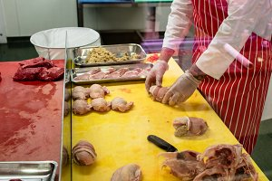 Mid section of butcher preparing a chicken and steak roll