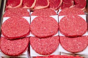 Raw hamburger patties on display
