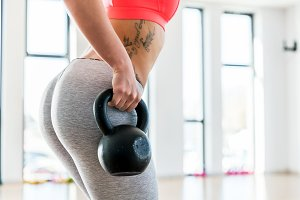 Fit woman holding a kettlebell.