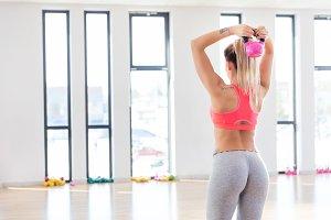 Fit woman doing a kettlebell workout.