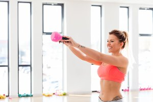Cheerful, fit woman doing a kettlebell swing.