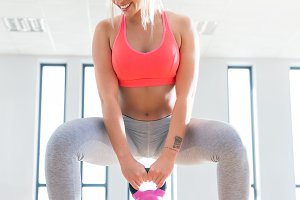 Fit woman doing a squat with kettlebell.