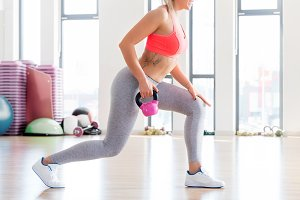 Fit woman doing lunge exercise with kettlebell.