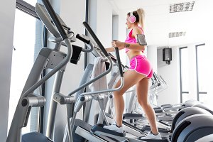 Woman training at crosstrainer in a gym.